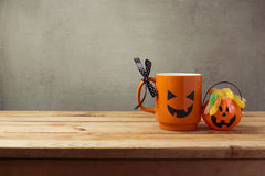 Coffee cup as jack o lantern pumpkin and candy for trick or treat on wooden table. Halloween concept Stock Images