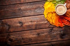 Coffee cup on the autumn leaves. And old wooden table background. Top view with copy space Royalty Free Stock Photo