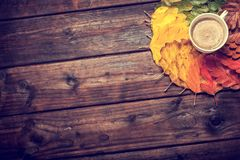 Coffee cup on the autumn leaves. And old wooden table background. Top view with copy space Stock Images