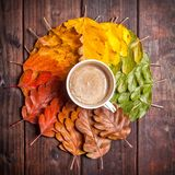 Coffee cup on the autumn leaves. And old wooden table background. Top view with copy space Royalty Free Stock Images