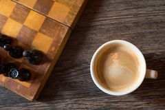 Coffee cup on the background of a chessboard. Top view