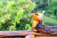 Coffee cup on bamboo coaster and wooden balcony with forest view Royalty Free Stock Photos