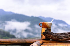 Coffee cup on bamboo coaster and wooden balcony with mountain view Stock Photography