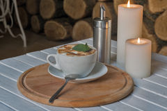 Coffee cup on bar table and romantic candles closeup Royalty Free Stock Images