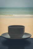 Coffee cup and beach. Coffee cups on table with beach and sea in background Royalty Free Stock Image