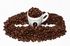 Coffee cup and bean shape. Espresso cup and coffee beans grouped together shaped as a bean on white background Royalty Free Stock Photography