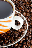 Coffee cup and beans. Coffee cup over coffee beans Royalty Free Stock Photos