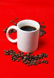 Coffee cup with beans 2. A filled cup of coffee with coffee beans aroung it on a red felt background Stock Photos