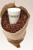 Coffee cup in beans. Coffee cup in sack of beans Royalty Free Stock Images
