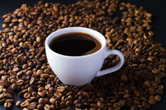 Coffee cup and beans. On a black background Royalty Free Stock Images