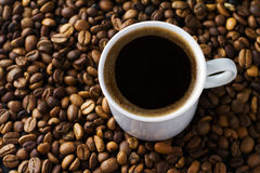 Coffee cup and beans. On a black background Royalty Free Stock Photo