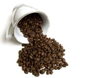 Coffee cup and beans. Laying coffee cup with spilled coffee beans stock images
