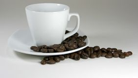 Coffee cup and beans. Cup of coffee with roasted beans Royalty Free Stock Photo