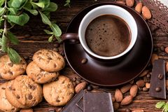 Coffee cup, beans, almond, chocolate and cookie on old kitchen table. Stock Image