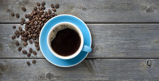 Coffee Cup Beans Background. A blue coffee cup full of black coffee on a wood background with coffee beans