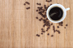 Coffee cup with beans on bamboo background Royalty Free Stock Images