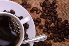 Coffee cup and beans. A cup of black coffee with coffee beans on the background Stock Images