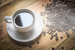 Coffee cup and beans on brown background Stock Image