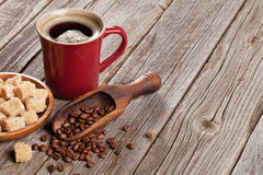 Coffee cup, beans and brown sugar on wooden table Royalty Free Stock Photography