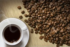 Coffee cup and beans on burlap Royalty Free Stock Photo
