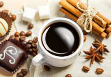 Coffee. Cup, beans, chocolate candy, cinnamon, sugar and anise on a table Royalty Free Stock Photo