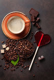 Coffee cup, beans, chocolate. And candy heart on stone background. Top view royalty free stock photography