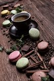 Coffee cup, beans, chocolate and color macaroons on the table. Stock Images