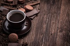 Coffee cup, beans, chocolate and macaroons on the table. Royalty Free Stock Image
