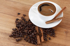 Coffee cup and beans, cinnamon sticks, anise on wooden table Royalty Free Stock Photography