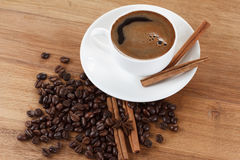 Coffee cup and beans, cinnamon sticks, anise on wooden table Royalty Free Stock Images