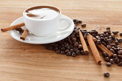 Coffee cup and beans, cinnamon sticks, anise on wooden table Stock Images