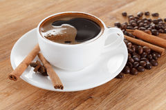 Coffee cup and beans, cinnamon sticks, anise on wooden table Stock Photos