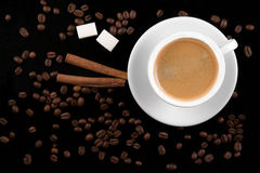 Coffee cup, beans, cinnamon sticks and sugar Royalty Free Stock Photos