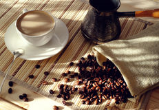 Coffee Cup with beans and a coffee pot. Cup of coffee with roasted beans. Morning sunlight and coffee. Breakfast with a Cup of coffee Stock Photo