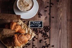 Coffee cup and coffee beans , croissant on brown wooden table Stock Photo