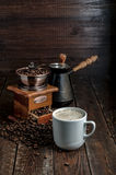 Coffee cup with beans, grinder and jezve on dark background Royalty Free Stock Photo