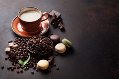 Coffee cup and beans. Coffee cup, beans and ground powder, chocolate and macaroons on stone background. With copy space for your text Stock Images