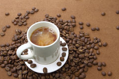 Coffee cup and beans on grunge wooden board Royalty Free Stock Photo