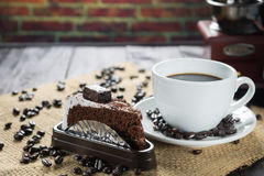 Coffee cup and beans on a rustic background. Coffee Espresso and. A piece of cake with a curl. Cup Of Coffee and coffee beans on table royalty free stock photos