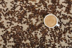 Coffee cup and beans on sacking background Stock Photo