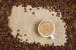 Coffee cup and beans on sacking background Stock Photography