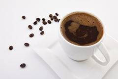 Coffee cup with beans scattered and isolated on a white background Stock Photos