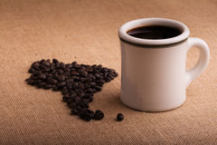 Coffee cup with beans in shape of South America on burlap Royalty Free Stock Image