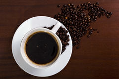 Coffee cup. A cup of coffee with coffee beans spilled Royalty Free Stock Photography