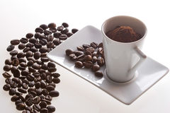 Coffee cup and beans on table. White coffee cup and plate with beans on table Stock Photos
