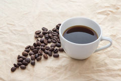Coffee cup and beans on table Royalty Free Stock Photos