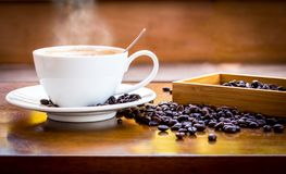 Coffee cup and coffee beans. On table with smoke royalty free stock photography
