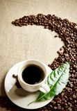 Coffee cup with beans twisted in a swirl on flax textile Stock Images