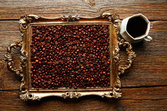 Coffee cup and beans on vintage golden tray. In wooden old table Royalty Free Stock Photos