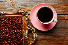 Coffee cup and beans on vintage golden tray. In wooden old table Royalty Free Stock Photo